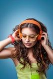 Muchacha con los ojos cerrados en auriculares que escucha la música Imágenes de archivo libres de regalías