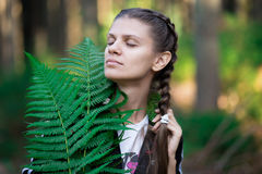 Muchacha con los ojos cerrados en un bosque imagen de archivo libre de regalías
