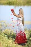 Muchacha con los pétalos color de rosa Foto de archivo libre de regalías