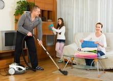 Muchacha con los padres que limpian en casa Fotos de archivo libres de regalías