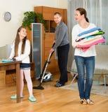 Muchacha con los padres que limpian en casa Foto de archivo libre de regalías