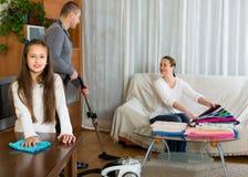 Muchacha con los padres que limpian en casa Fotografía de archivo libre de regalías
