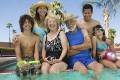 Muchacha (10-12) con los padres y los abuelos del hermano (13-15) en el retrato de la piscina. Imagen de archivo