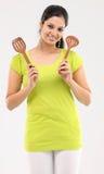 Muchacha con los palillos de madera usados en cocina Foto de archivo