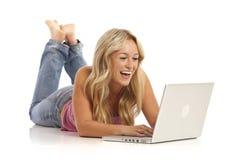 Muchacha con los pantalones vaqueros que ponen en suelo con la computadora portátil Foto de archivo libre de regalías