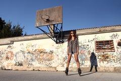 Muchacha con los pcteres de ruedas en fondo de la pintada y un baloncesto Fotos de archivo