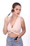 Muchacha con los pendientes y la presentación del cepillo del maquillaje Cierre para arriba Fondo blanco Fotos de archivo libres de regalías