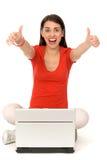 Muchacha con los pulgares para arriba usando la computadora portátil Fotos de archivo libres de regalías