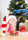 Muchacha con los regalos cerca de un árbol del Año Nuevo Foto de archivo