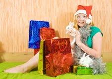 Muchacha con los regalos y los conejos de la Navidad Fotografía de archivo libre de regalías