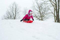 Muchacha con los trineos al aire libre el día de invierno Fotografía de archivo