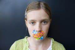 Muchacha con los vendajes sobre su boca imagenes de archivo