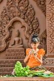 Muchacha con los vestidos tradicionales que doblan el pétalo del loto Fotos de archivo libres de regalías