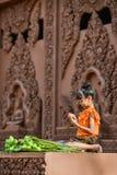 Muchacha con los vestidos tradicionales que doblan el pétalo del loto Fotografía de archivo