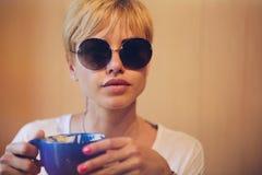 Muchacha con los vidrios con café Imagen de archivo libre de regalías