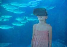 muchacha con los vidrios de VR en el mar con los pescados foto de archivo libre de regalías