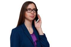 Muchacha con los vidrios que habla en el teléfono Imágenes de archivo libres de regalías