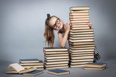 Muchacha con los vidrios que lee un libro Imágenes de archivo libres de regalías