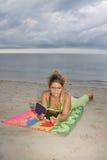Muchacha con los vidrios que lee un libro (vert) Imagen de archivo libre de regalías