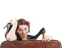 Muchacha con los zapatos en manos detrás de la maleta Fotos de archivo libres de regalías