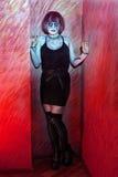 Muchacha con los zombis del maquillaje que se colocan en pared roja Fotos de archivo libres de regalías
