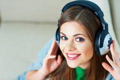 Muchacha con música que escucha de los auriculares en casa Imágenes de archivo libres de regalías