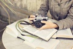 Muchacha con muchos libros abiertos y cámara del viejo estilo Fotografía de archivo libre de regalías