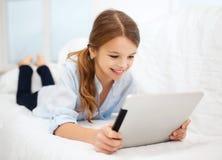 Muchacha con PC de la tableta en casa Fotos de archivo libres de regalías