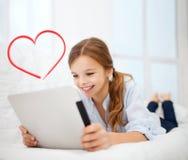 Muchacha con PC de la tableta en casa Fotografía de archivo