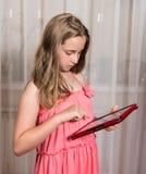Muchacha con PC de la tableta en casa Foto de archivo