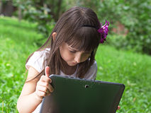Muchacha con PC de la tableta en el prado Imagen de archivo libre de regalías