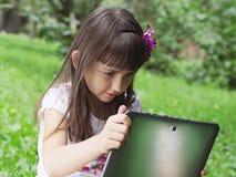 Muchacha con PC de la tableta en el prado Foto de archivo libre de regalías