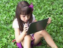 Muchacha con PC de la tableta en el prado Fotos de archivo libres de regalías