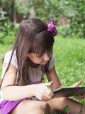 Muchacha con PC de la tableta en el prado Fotos de archivo