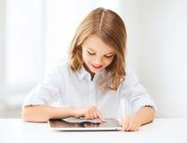 Muchacha con PC de la tableta en la escuela Imagen de archivo