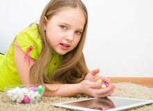 Muchacha con PC de la tableta y los caramelos coloreados Imagen de archivo