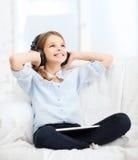 Muchacha con PC y los auriculares de la tableta en casa Imagen de archivo libre de regalías