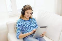 Muchacha con PC y los auriculares de la tableta en casa Fotos de archivo