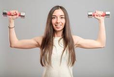 Muchacha con pesas de gimnasia Imágenes de archivo libres de regalías