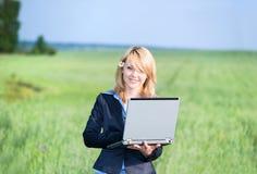 Muchacha con retén de la computadora portátil en prado foto de archivo libre de regalías