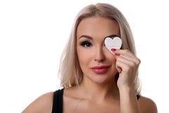 Muchacha con símbolo del corazón en su ojo Cierre para arriba Fondo blanco Foto de archivo