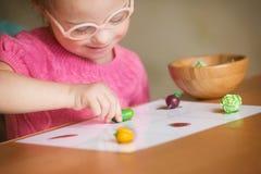 Muchacha con Síndrome de Down con el interés que clasifica verduras Imagen de archivo libre de regalías