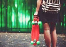 Muchacha con shortboard anaranjado plástico del penique detrás de la pared verde en casquillo Fotos de archivo