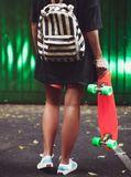 Muchacha con shortboard anaranjado plástico del penique detrás de la pared verde en casquillo Foto de archivo libre de regalías
