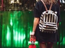 Muchacha con shortboard anaranjado plástico del penique detrás de la pared verde en casquillo Imagen de archivo libre de regalías