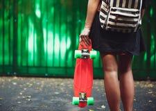 Muchacha con shortboard anaranjado plástico del penique detrás de la pared verde en casquillo Imágenes de archivo libres de regalías