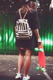 Muchacha con shortboard anaranjado plástico del penique detrás de la pared verde en casquillo Foto de archivo