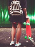 Muchacha con shortboard anaranjado plástico del penique detrás de la pared verde en casquillo Imagenes de archivo