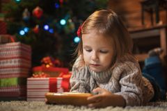 Muchacha con smartphone en casa con un árbol de navidad, presentes y Foto de archivo libre de regalías