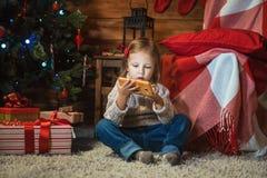 Muchacha con smartphone en casa con un árbol de navidad, presentes y Imagen de archivo libre de regalías